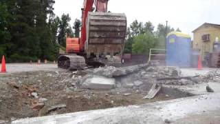 Excavator ripping up concrete