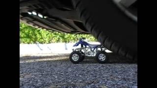 Jennifer crushes a toy quad bike under car tyres (slow motion)