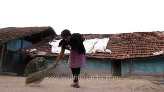 Woman sweeping her house at Madai village, Satpura