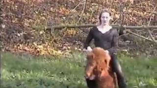 Woman riding very small pony