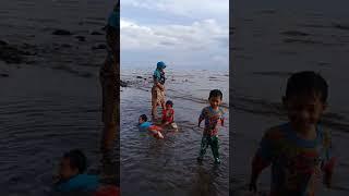 Anak ou saro mandi di pantai.