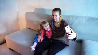 Young mother of American descent sits on sofa with small daughter and makes photo on phone