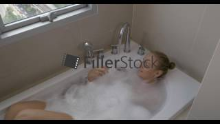 Woman in bath relaxing from big city. Window view to Bangkok, Thailand