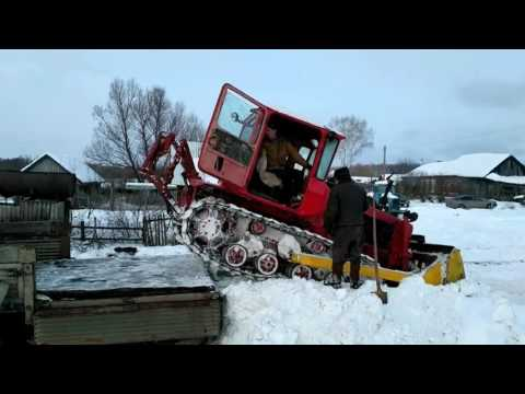 Russians load a tractor on a truck without crane or any other mechanism