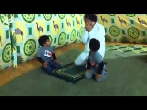 معمر القذافي يضحك في الصلاة ويلاعب أحفاده