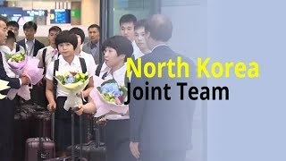 North Korean table tennis players arrive in South Korea with bouquets in hand.