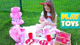 Girl playing with silicon baby doll - change diaper, feed baby and  kids car ride on hot wheels