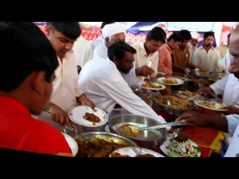Men grabbing food at a wedding reception in Pakistan