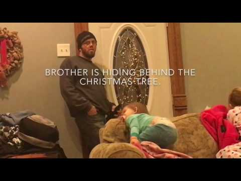 Army brother hides behind Christmas tree to surprise sisters.