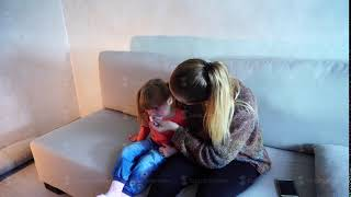 Blonde young mother sitting on couch and wiping nose small daughter