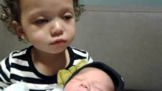 Toddler trying to breastfeed her new baby cousin