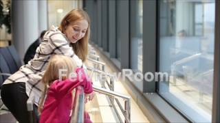 Young mother and small daughter are watching through the window in the airport