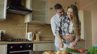 Happy young couple in the kitchen. Attractive cooking woman feeding her boyfriend in the morning