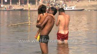 Hindu father bathes daughter in Ganga, to cleanse and obsolve of sin at Varanasi