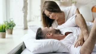 Young beautiful and loving couple wake up at the morning. Attractive woman kiss and hug his husband