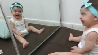 Baby having Fun seeing self for the first time in the mirror