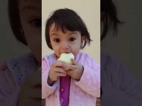 Little girl eats onion like a boss