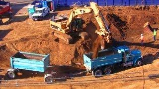 Excavator Fills Dump Trucks with Dirt at Construction Site