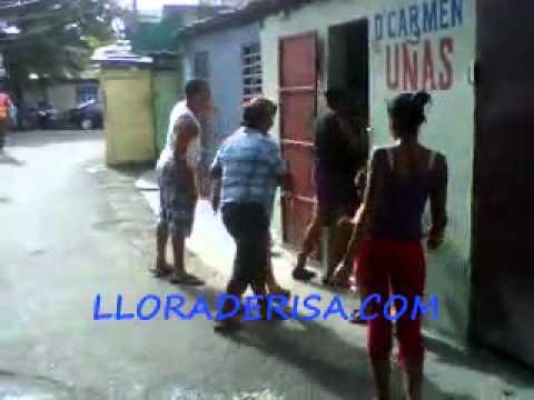 Mujeres se dan ata con la mano del pilon en el medio de la calle