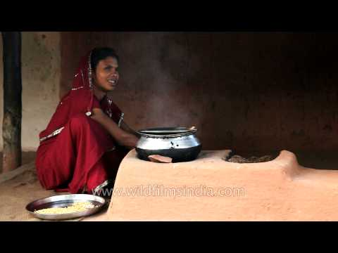 Indian woman cooks food on a traditional stove (chulha)