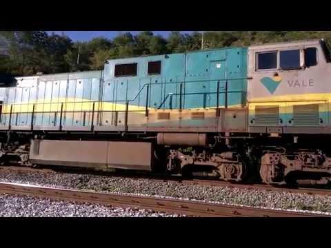 Trem cargueiro de minério de ferro subindo para com a locomotiva intermediária de frente pra mim.
