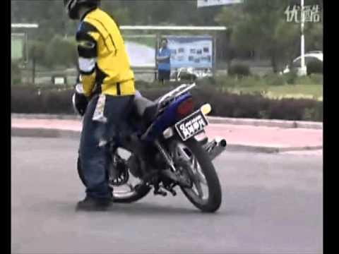 Destreza acrobática sobre una Suzuki EN 125 moto