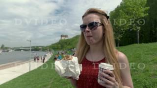 Blonde girl in sunglasses eating appetizing sandwich on summer day
