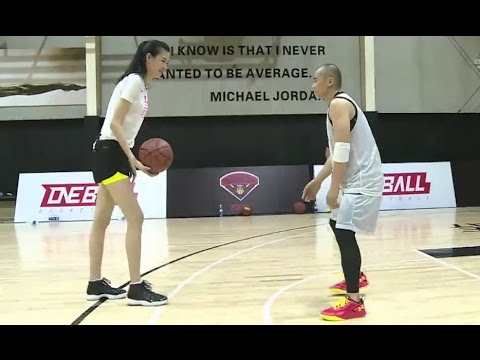 Tall Woman Plays Basketball with Shorter Guy
