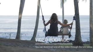 Child and young mother enjoying a swing and laughing under the palm tree. Video stock footage