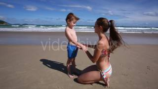 Young Mother Does Sunscreen of Her Son on the Beach