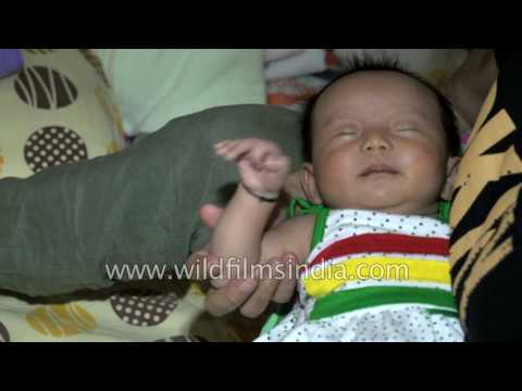 Indian Mother changes diaper of her wailing infant daughter, kid falls asleep