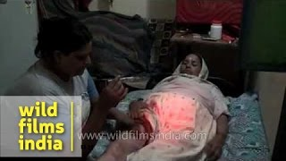 Indian hijra injects insulin into her mother's thigh