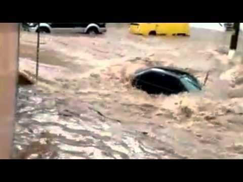Homem se segura para não ser levado por enchente na Grande São Paulo