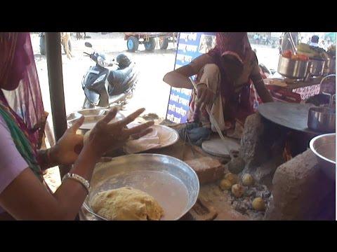 VILLAGE Women MAKING  DAL BATI - (RAJASTHANI FOOD ) over a mud stove in Pushkar, Rajasthan
