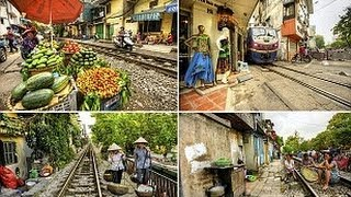 Railway line runs through streets so narrow the train squeezes past shop fronts and traders