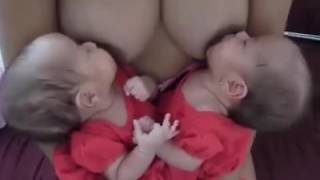 Young Mother feeding milk to her 2 baby openly in openly.