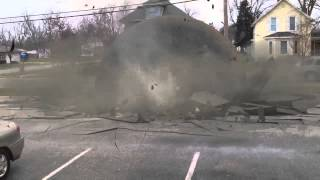 Car crushed by big metal ball right in front of house