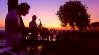 Saxophonist playing in the sunset with a DJ