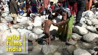 Mother bathing kid in freezing water of river Ganga at Gangotri
