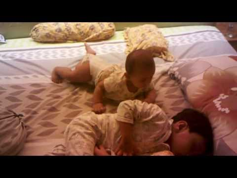 Sister playing with sleeping brother