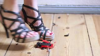 Girl in heels crushing toy car