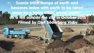 Scania truck dumps of earth and becomes laden with earth to be taken away by a Volvo L120C wheel loa