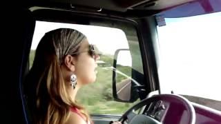 Mulher dirigindo carreta e cantando