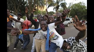 Zimbabweans dance and sing at the news of Robert Mugabe