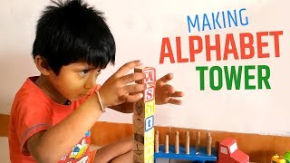 Three year old boy making tower of alphabets (cubes) with amazing level of concertration