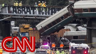 Derailed Amtrak train dangles over highway in Washington