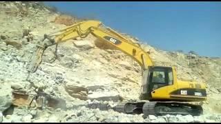 Excavadora 320cl picando piedra caliza