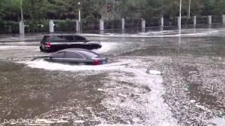 Hot Japanese Girl Driving Car Through Flooded Street