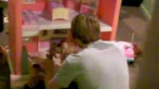 Disturbed boy playing with barbies