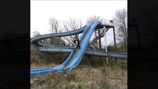 guy bikes down a tall water slide